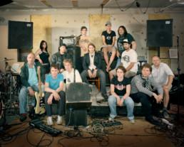 Inszeniertes Gruppenbild von Mitglieder und Mitgliederinnen unterschiedlichster Musikrichtungen von einem Rockförderverein. Alle sitzen oder stehen sie auf der kleinen vollgestopften Probebühne in einem Bandkeller.