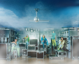 Inszeniertes Gruppenbild von Mitgliederinnen eines DJanes-Vereins. Die Frauen sitzen auf den Verpackungskoffern in einem Lagerkeller mit Beleuchtungssystemen für Events und Konzerte. Künstlicher Rauch ist im Raum.