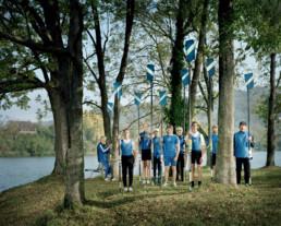 Inszeniertes Gruppenbild von Mitglieder*innen eines Ruderclubs. Sie stehen in ihrer Vereins-Ruder-Kleidung am Ufer von einem Fluss zwischen den Bäumen. Jede/r hat ein Riemen in der Hand.