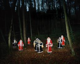 Inszeniertes Gruppenbild von mehreren Santikläusen und Schmutzlis in einem dunklen Wald. Sie stehen in ihrer Santiklause -Kleidung mit ihren vollgefüllten Säcken und Ruten zwischen den Bäumen.