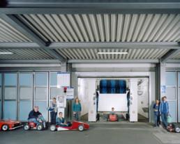 Inszeniertes Gruppenbild von Mitglieder eines Seifenkistenvereins. Alle sitzen in ihren selbstgebauten Seifenkisten-Autos in einer Auto-Waschanlage.