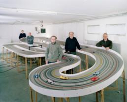 Inszeniertes Gruppenbild von Männer eines Slot-Car-Racing-Clubs. In einem Keller habe sie ihre Modellautorennbahn aufgebaut und stehen ringsum.