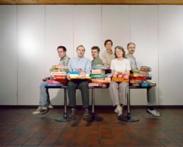 Inszeniertes Gruppenbild von Mitglieder eines Spieltreffs. Die Männer und Frauen sitzen alle in einem Saal auf einem grossen Tisch. Zwischen ihnen und auf Ihrer Schoss sind Schachteln von Brettspiele aufgetürmt.
