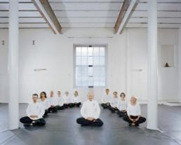Inszeniertes Gruppenbild von Teilnehmer*innen von einem Taiji und Qigong Kurs. Alle sitzen in einem Halbkreis in einem grossen, hellen Raum.