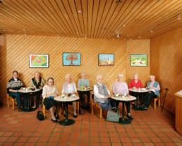 nszeniertes Gruppenbild von meist älteren Damen, welche in einem getäferten Raum verteilt mit Ihren Strickarbeiten an kleinen Tischen sitzen.