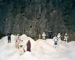 Inszeniertes Gruppenbild von Mitglieder einer Star-Wars- Gruppe. An einem futuristischen kargen Ort stehen die als Star-wars Figuren verkleideten Menschen. Im Hintergrund eine hohe dunkle Stein-Wand.
