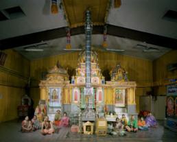 Inszeniertes Gruppenbild von Mitglieder eines Tamilischen Vereins in einer grossen Industriehalle, in welcher ein Tamilischer Tempel aufgebaut ist. Im Vordergrund sitzen die Männer und Frauen in ihren bunten Saris.