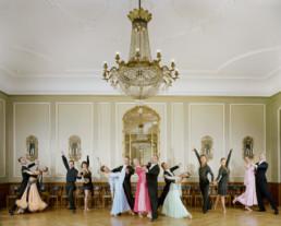 Inszeniertes Gruppenbild von Standardtänzerinnen und -Tänzer in ihren schicken Tanzkleider in einem edlen Ballsaal mit einem grossen Leuchter.