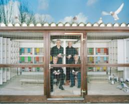 Inszeniertes Gruppenbild von Mitglieder eines Taubenzüchtervereins. Die Männer sitzen und stehen hinter Gitter in einem Taubenschlag.