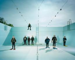 Inszeniertes Gruppenbild von Mitglieder von einem Tauchclub. Die Männer und Frauen stehen in ihren Taucheranzügen, mit Brille, Schnorchel und Tauchfalschen in einem leeren, tiefen Schwimmbadbecken.