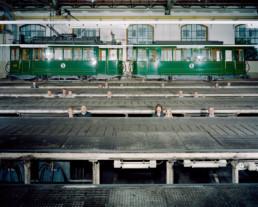 Inszeniertes Gruppenbild von Mitglieder von einem Tramclub. Die Mitglieder*innen stehen in der Unterhaltsgrube, sodass nur die Köpfe herausschauen. Im Hintergrund steht ein altes Tram.