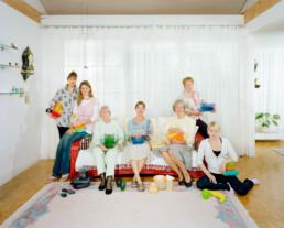 Inszeniertes Gruppenbild von Mitgliederinnen eines Tupperware-Clubs. Die Damen sitzen alle auf einem Sofa in einem hellen Wohnzimmer. Auf Ihren Knien haben sie Tupperware-Produkte.