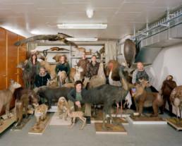 Inszeniertes Gruppenbild von Mitglieder eines Präparatorenverbands. In einem Keller-Archiv sitzen und stehen die Präparatorinnen mitten zwischen vielen präparierten Tieren.