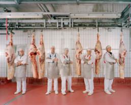 Inszeniertes Gruppenbild von Metzger, welche mit Ihrer Ausrüstung und in der Metzgerkleidung zwischen aufgehängten halben Seiten von Tieren stehen.