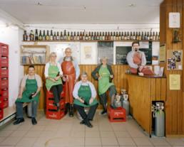 Inszeniertes Gruppenbild von Mitglieder von einem Bierbrau-Verein. Sie sitzen und stehen in Ihrer Brauküche. Ringsum Harassen und Brauutensilien