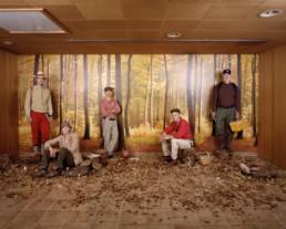 Inszeniertes Gruppenbild von Mitglieder von einem Pilzkunde-Verein. Die Männer und Frauen stehen in einem braunen Raum vor einer Herbstwaldtapete. Am Boden viel Laub und Pilze.