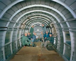 Inszeniertes Gruppenbild von Mitglieder von einem Club, welche ein altes Flugzeug renovieren. Sie sitzen in ihren Mechaniker-Overalls im leeren Flugzeugrumpf.
