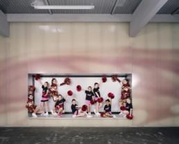 Inszeniertes Gruppenbild von Cheerleaderinnen, welche zusammen in ihren Auftrittskostümen posieren.
