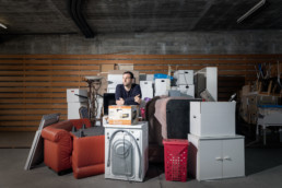 In einer Lagerhalle ist ein grosser Teil von einem Hausrat zusammengestellt. Dazwischen steht ein Herr, der Hüter der Räumungsobjekte.