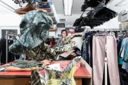 In einem Raum von einer Kleidersammelstelle hängen viele Kleider. Eine Mitarbeitern steht zwischen den Hosen, Hemden und Blusen.