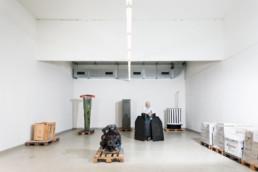 In einem grossen, hellen Raum stehen einzeln verteilt diverse Objekte von einer Sammlung der Polizei. Ein Mann, welcher für die Sammlung zuständig ist steht hinter einem Objekt.