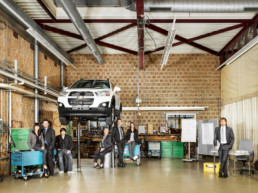 In einer Auto-Werkstatt ist ein Auto aufgebockt. In der Werkstatt stehen Mitarbeitende herum, welche einen Weiterbildungskurs besuchen.