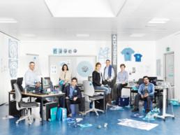 In einem Schulzimmer mit blauem Linoleum-Boden stehen Bürotische und Stühle, Drucker, Ordner, Büromaterial, Papier, Stifte herum. Dazwischen sitzen erwachsene Leute, welche an einem Kurs für Desktop Publisher teilnehmen.