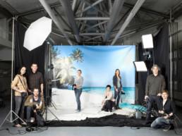 In einem grossen Foto-Studio der Migros-Klubschule ist ein Hintergrundrolle mit einem Palmenstrand-Bild aufgebaut. Das Set ist mit vielen Lampen, schwarzen Tüchern und Stativen ausgestattet. Mittendrin und ringsum posieren die Kursteilnehmenden mit Ihren Kameras.