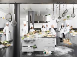 In einer grossen, modernen Schulküche stehen erwachsene Kursteilnehmende in Ihren Kochjacken und mit ihren Kochmützen. Die ganze Küche ist voll Esswaren, es dampft und raucht aus allen Töpfen und Schubladen hervor.