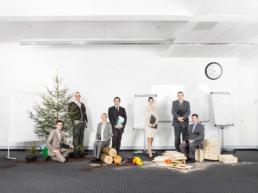 In einem Klassenzimmer sind die Objekte für einen Projektablauf -vom Baum zum Möbel- zu sehen. Darum stehen gut gekleidete Business-Leute, alles Teilnehmende des Kurses für Projektmanagement.