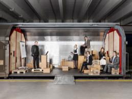 In einem Güterwagon, der seitlich offen ist, ist aus Holz und Kartonkisten ein Klassenzimmer aufgebaut. Darin steht ein Lehrer neben seinem Flip-Chart. Die erwachsenen Kursteilnehmer des Kurses 'Sachbearbeiter Export' sitzen auf Kisten und Schachteln, mit Ihrem Schulmaterial