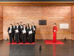 In einem Raum aus rotem Backstein sind zwei rote Teppiche ausgelegt. Auf dem rechten steht eine Chinesisch-Lehrerin, auf dem linken Ihre Schülerinnen und Studenten, mit chinesischen Schriften in der Hand.