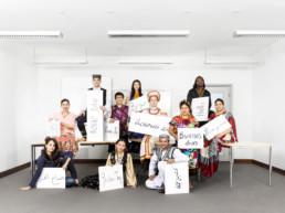 In einem weissen Klassenzimmer sitzen viele Menschen aus aller Welt zusammen und nehmen an einem Kurs für die Sprache Deutsch teil. Sie tragen alle traditionelle Kleidung und halten ein Schild in der Hand, auf welchem 'Guten Tag' in ihrer Landessprache geschrieben steht.