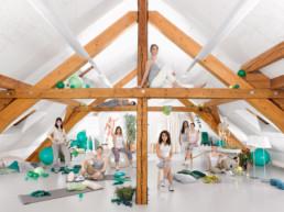 In einem ausgebauten Dachstock findet der Klubschule Migros Kurs zur Trainer/in 'Bewegung und Gesundheit' statt. Kursteilnehmende sitzen und stehen im Raum zwischen vielen Yoga-matten, Gymnastik-Bälle, Pflanzen und weiterem Material.