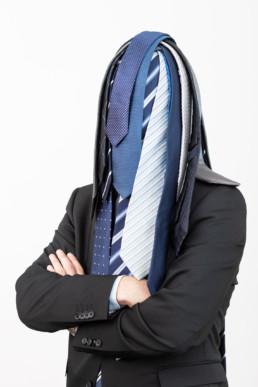 Ein Mann steht vor einem hellen Hintergrund. Unzähligen Krawatten liegen auf seinem Kopf und verdecken sein Gesicht.