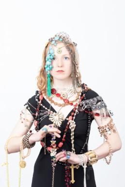 Eine Frau in einem schwarzen Kleid steht mit dem Rücken zur Kamera vor einem hellen Hintergrund. Sie träg viel Schmuck, auf dem Kopf, bis zu den Armen und Händen.