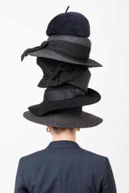 Eine Frau steht, mit dem Rücken zu uns, vor einem hellen Hintergrund. Auf ihrem Kopf trägt sie mehrere Hüte aufeinandergestapelt.
