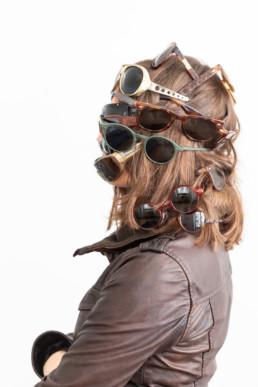 Vor einem hellen Hintergrund steht eine Frau. Sie trägt sehr viele Brillen übereinander, sodass ihr Gesicht fast nicht zu sehen ist.