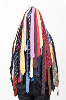 Ein Mann steht vor einem hellen Hintergrund. Er ist verdeckt von unzähligen bunten Krawatten.