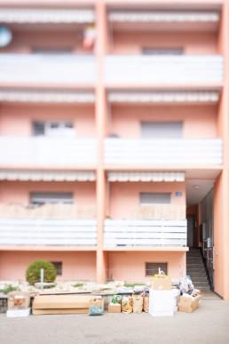 Vor einem rosaroten Mehrfamilienhaus steht das Altpapier zum abholen bereit.