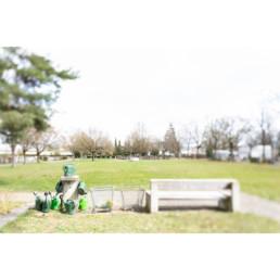 Auf einem Friedhof sind die Giesskannen ordentlich zur Benutzung zusammengestellt.