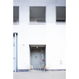 Auf einer Strasse stehen in einem Hintereingang von einem Einkaufszentrum ein paar Stühle zusammen. Es ist ein Pausenort für Mitarbeitenden.