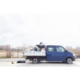 Auf einer Strasse steht vor einem Feld einen mit Müll gefüllten Pickup. Ein Schuh liegt daneben.